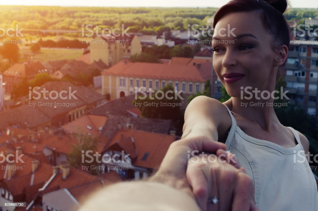 man holding woman hand above the big city stock photo