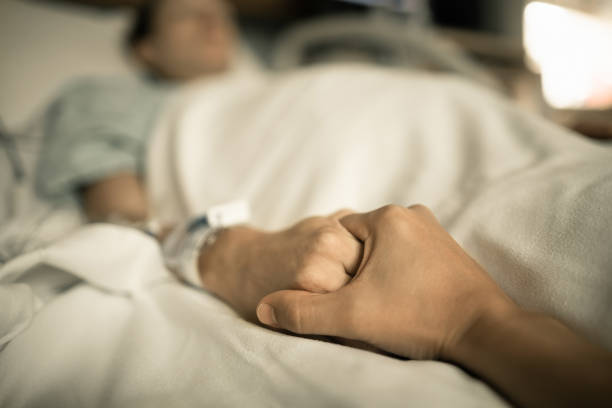 Man holding woman hand in hospital bed. Holding hands in hospital bed stock photo