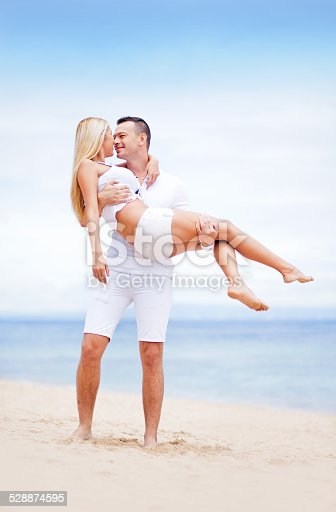 1065243116 istock photo Man holding woman in his arms 528874595