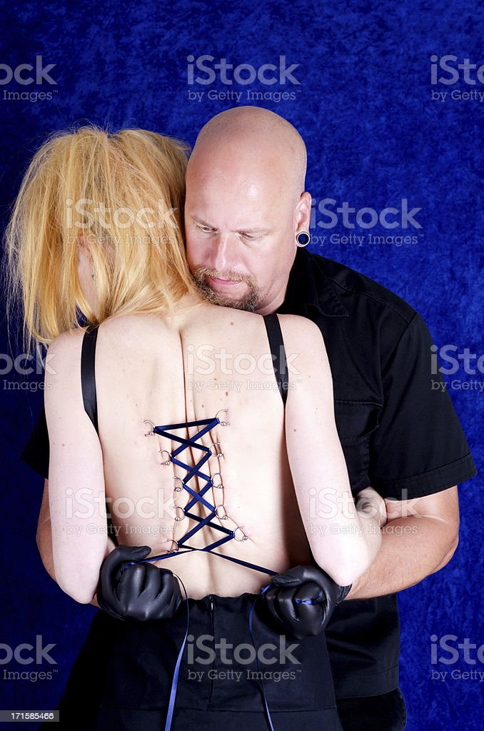 Man holding woman, pulling on corset piercing laces. stock photo