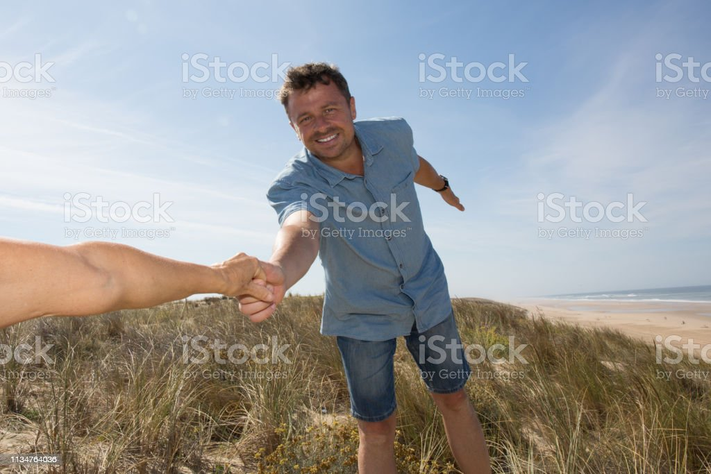 Man holding woman\'s hand and leading him on ocean outdoor. Couple in...