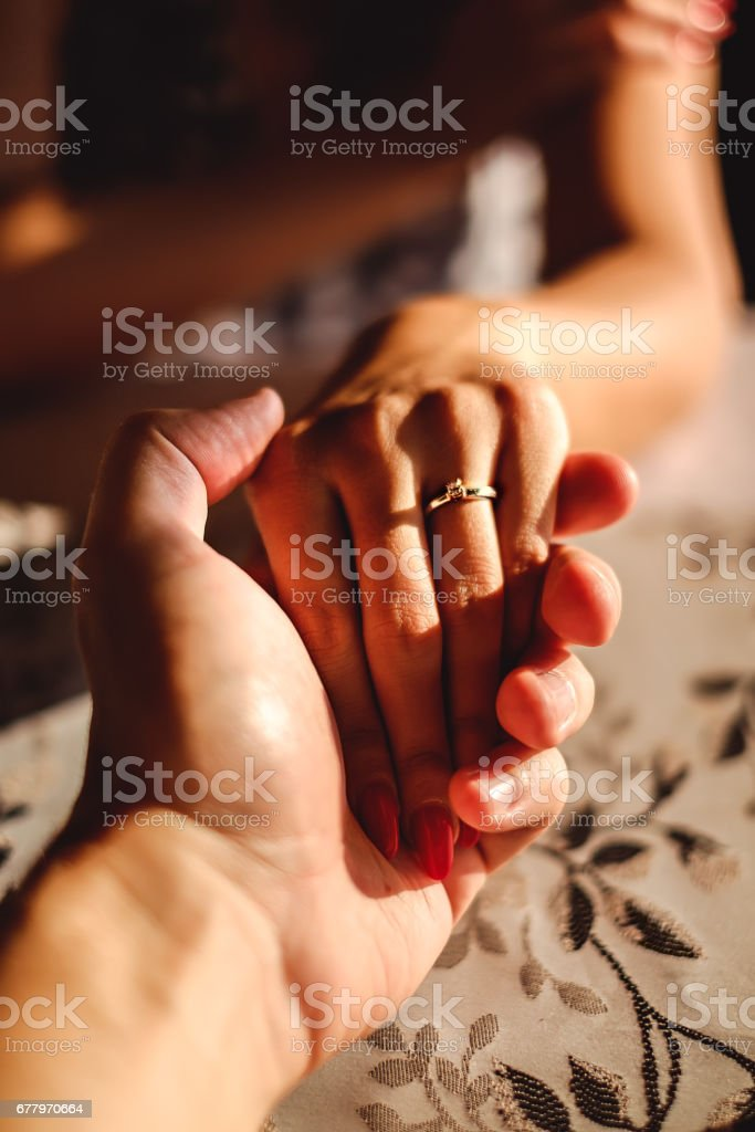 Man holding woman's hand with wedding ring on the finger royalty-free stock photo