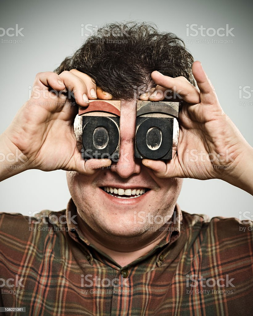 Man Holding Wooden Stamps to Eyes royalty-free stock photo