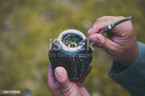 istock Man holding yerba mate in nature. Travel and adventure concept. Latin American drink yerba mate 1081742940