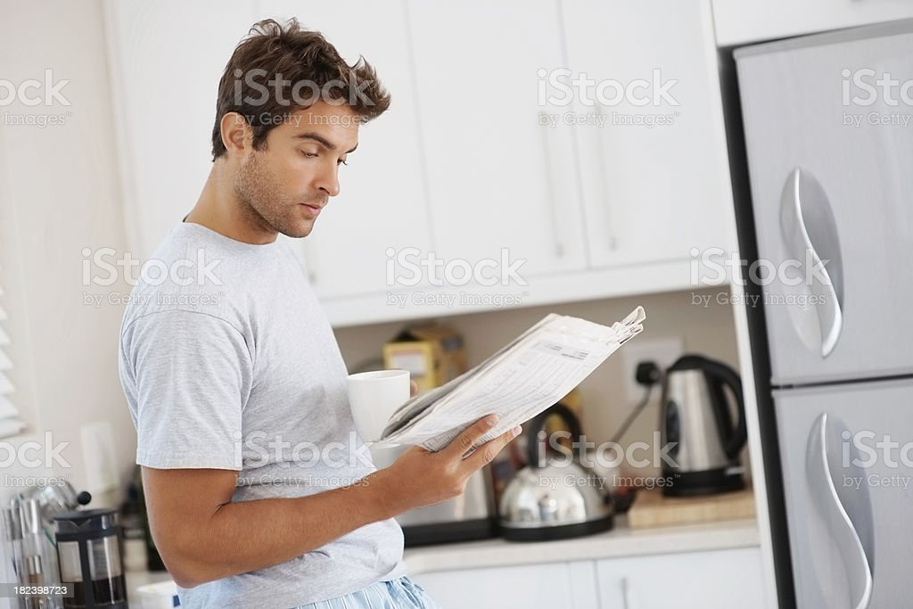 Man holdoing a cup of coffee and reading news paper royalty-free stock photo