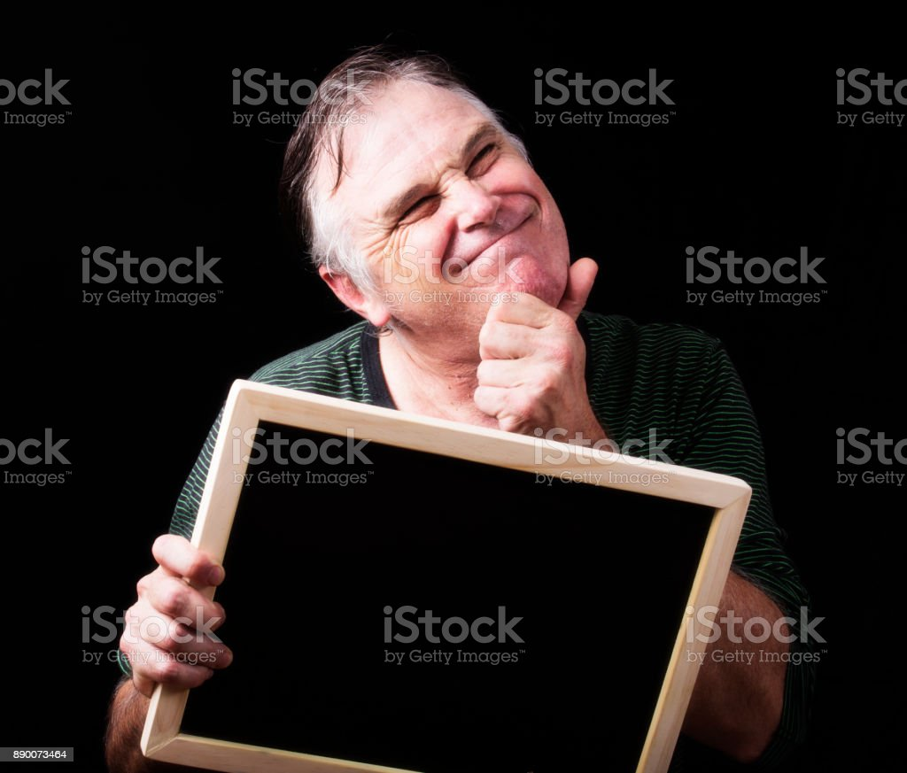 Man holds a blank black board with copyspace and looks satisfied stock photo