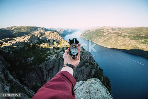 A man holds a compass in his left hand overlooking on Lysefjord