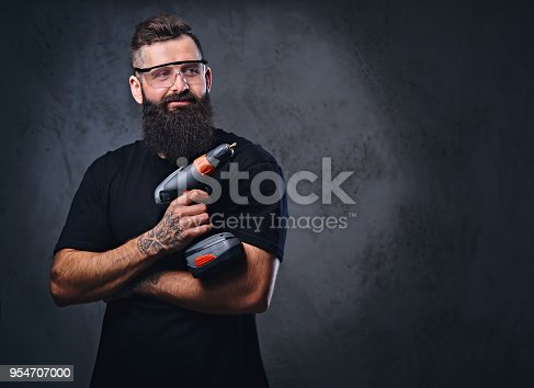 istock A man holds a drill over grey background. 954707000