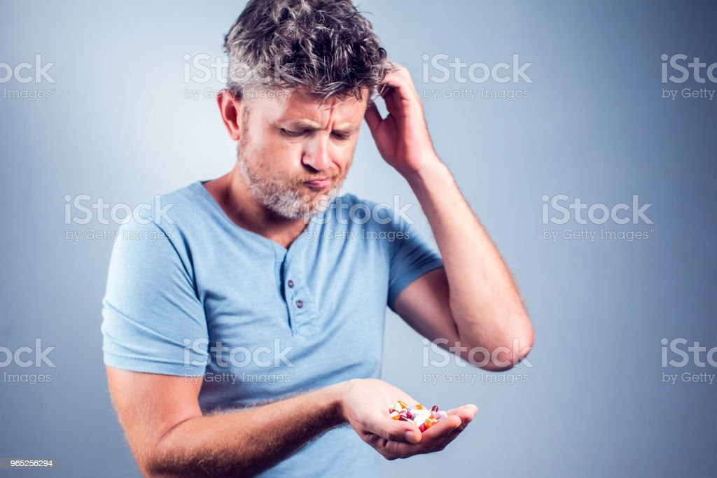 A man holds a lot of colored pills in hands. Health care and medicine concept zbiór zdjęć royalty-free