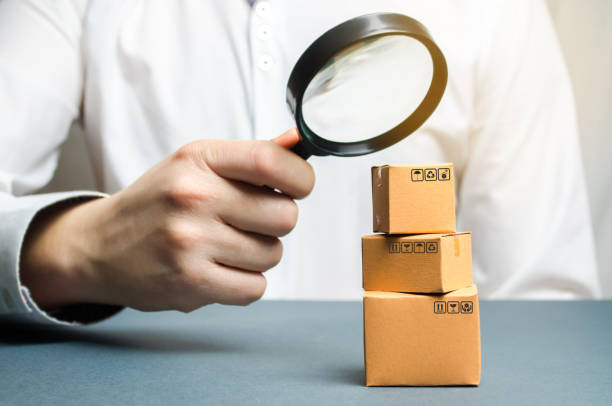 a man holds a magnifying glass above the boxes. examination of goods for the presence of contraband, prohibited goods, defects. quality control, authentication. study of consumer sentiment - defects stock pictures, royalty-free photos & images