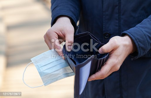 Man holds a medical mask and empty wallet without money. Bankruptcy and unemployment resulting from the global coronavirus or covid-19 epidemic.