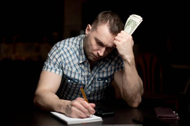 hombre tiene una cantidad modesta de dinero y hace notas en un cuaderno - foto de stock