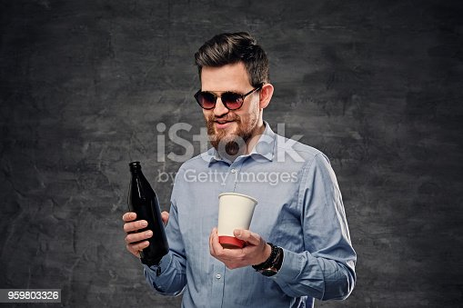 The elegant bearded hipster male holds a paper coffee cup and craft bottled beer.