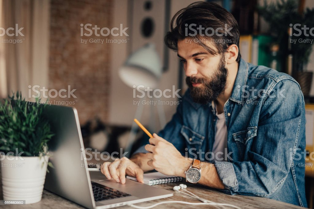 A man holds a pen and uses laptop stock photo
