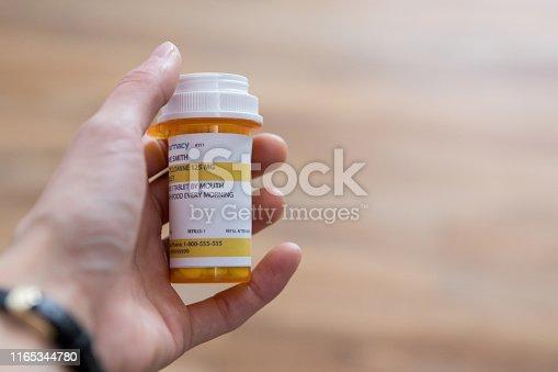 Unrecognizable man holds a pill bottle containing prescription medication.