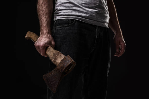 a man holds an ax in his hands against on black background - killer stock pictures, royalty-free photos & images