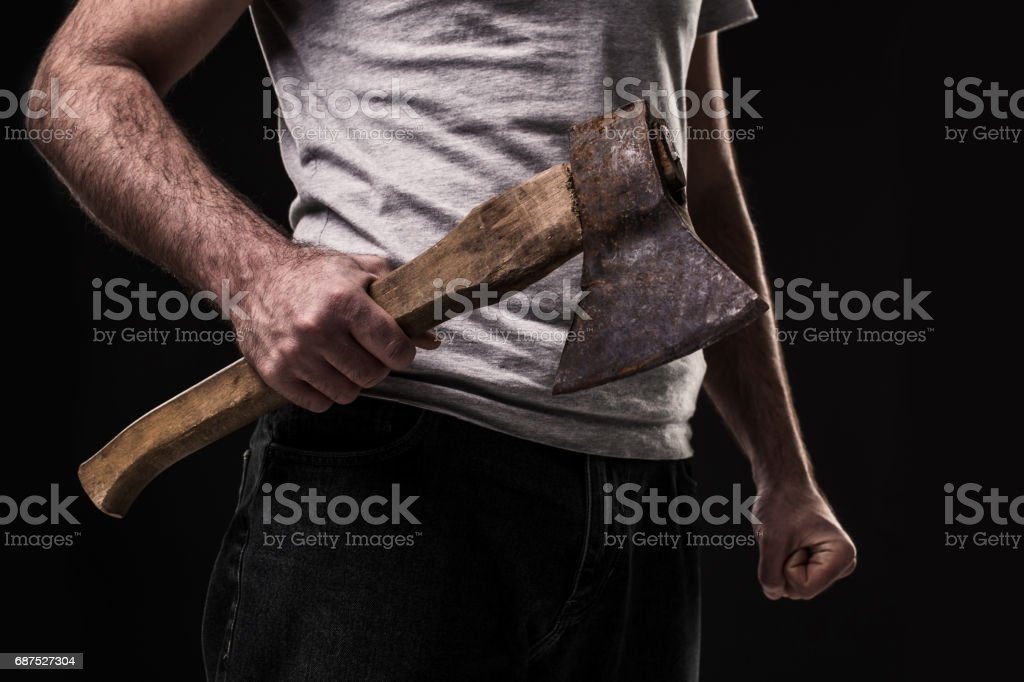 A man holds an ax in his hands against on black background stock photo