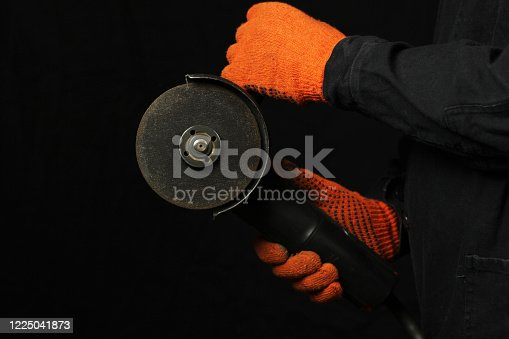A man holds an electric saw in his hands on a black background