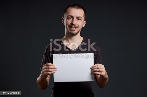 1048561956 istock photo Man holds an empty poster paper sheet in his hands. Smile and joy, place for text, copy space 1217785063