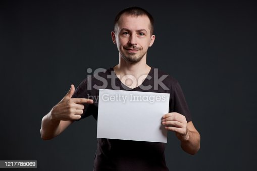 1048561956 istock photo Man holds an empty poster paper sheet in his hands. Smile and joy, place for text, copy space 1217785069