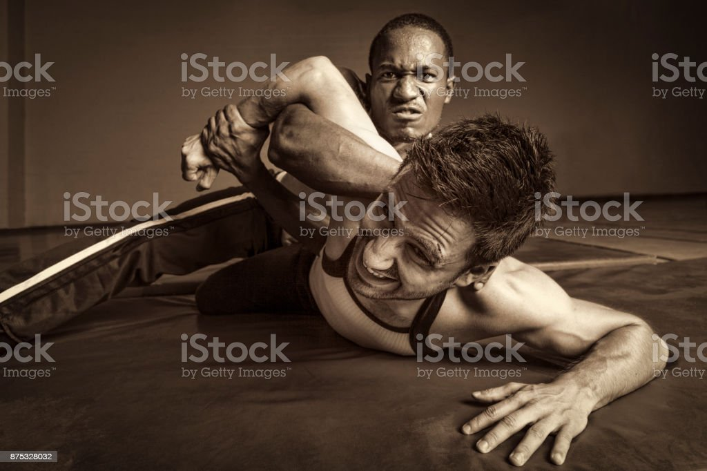 Man holds another man down in a wrestling match stock photo