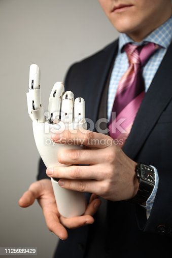 istock Man holds artificial limb for disabled people. Prosthetic arm 1125939429