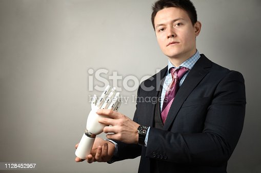 istock Man holds artificial limb for disabled people. Prosthetic arm 1128452957