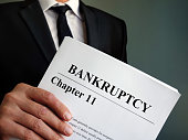 Man holds Bankruptcy Chapter 11 agreement documents.