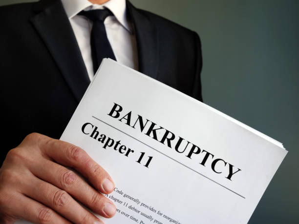 man holds bankruptcy chapter 11 agreement documents. - bankruptcy stock pictures, royalty-free photos & images