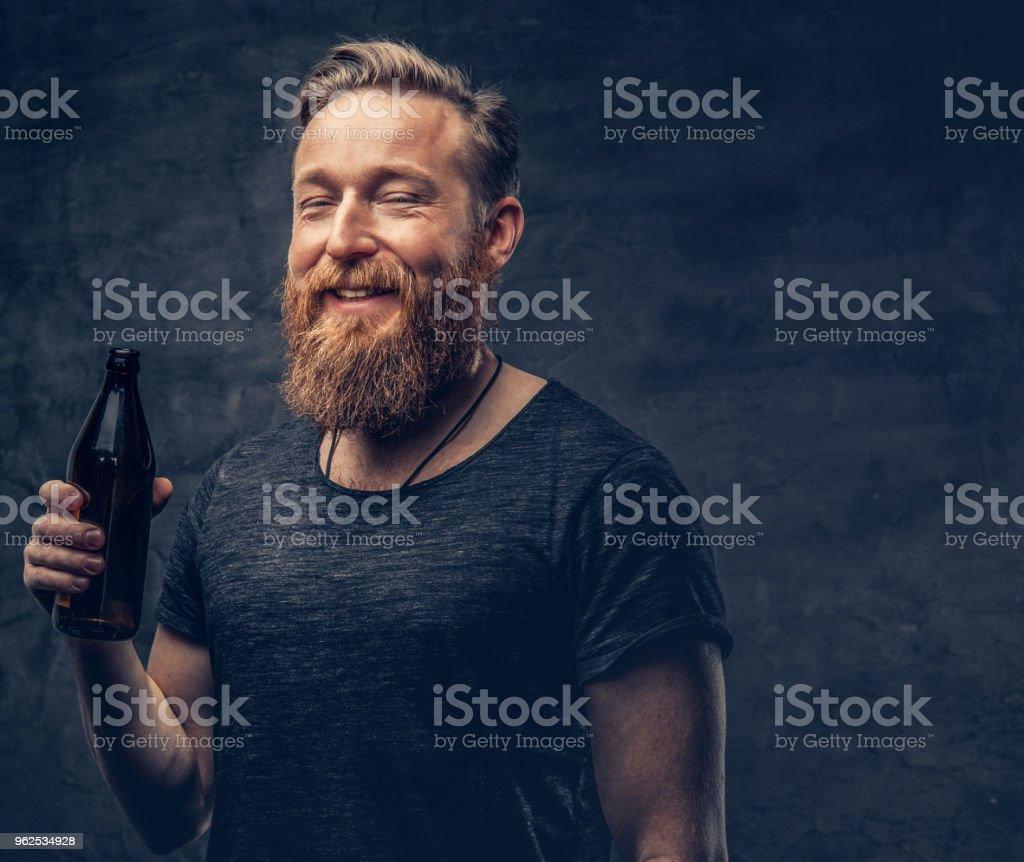 Um homem mantém a garrafa de cerveja. - Foto de stock de Alcoolismo royalty-free
