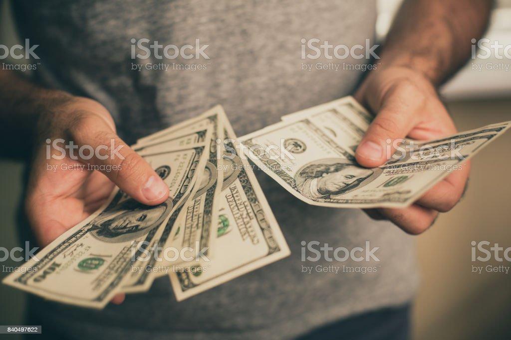 一個男人他手裡拿著美元 - 免版稅Dollar Store圖庫照片