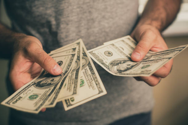 a man holds dollars in his hands - coin stock photos and pictures