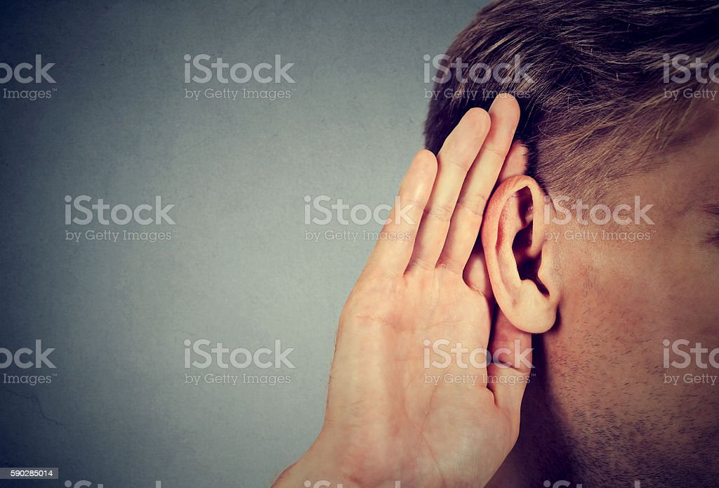 man holds hand near ear and listens carefully stock photo