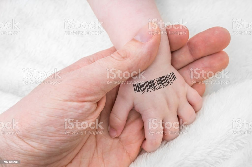 Man holds hand of a baby with bar code on it. Genetic cloning concept. stock photo