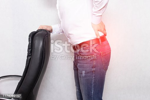 A man holds his back holding an office chair concept of back pain, pinched nerve and myofascial syndrome, osteochondrosis, vertebra