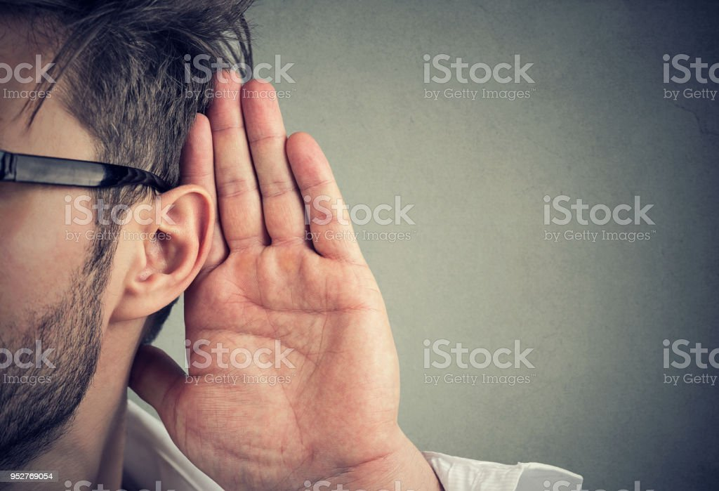 man holds his hand near ear and listens carefully stock photo
