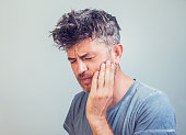 Man holds his hand near the cheek toothache