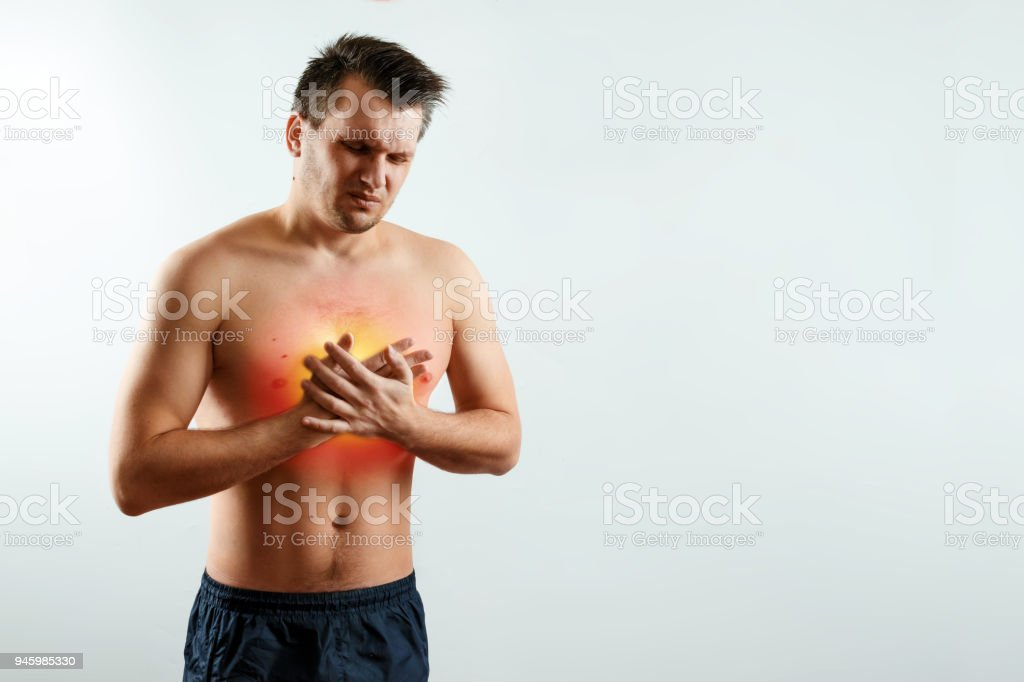 A man holds his hands and region of the heart, chest pain, a pain in the heart highlighted in red, a heart attack. Light background. The concept of medicine, massage, physiotherapy, health. stock photo