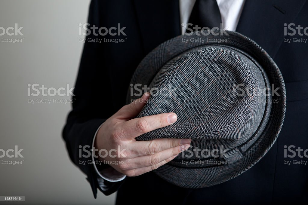 Man holds his hat against body stock photo