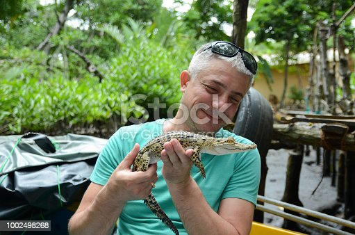 A man holds in hands a small crocodile. Jungle of Sri Lanka