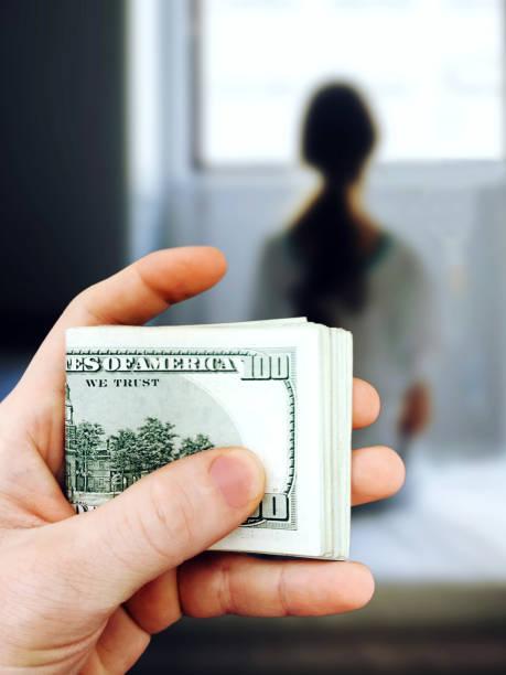 el hombre tiene en su mano un paquete de billetes de cien dólares en el fondo de la chica que van a vender a la esclavitud. el concepto de violencia, trata de personas. mixtas - human trafficking fotografías e imágenes de stock