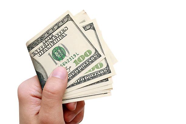 Mann hält seine hand einen Hundert-Dollar und zahlt – Foto