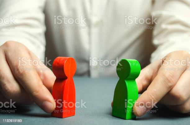 A Man Holds In His Hands The Red And Green Figures Of People Facing Each Other Conflict Resolution Conflict Of Interest The Search For A Compromise Mediation In Negotiations Weave Intrigue — стоковые фотографии и другие картинки Бизнес