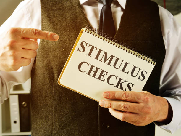 Man holds information about Coronavirus stimulus checks. Man holds information about Coronavirus stimulus checks. stimulus check stock pictures, royalty-free photos & images