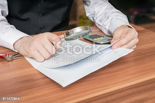 istock Man holds magnifying glass and is reading contract. 511472914