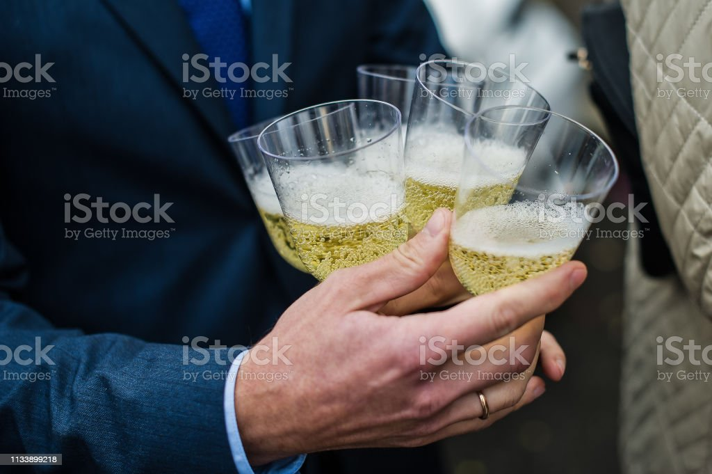 A man holds many glasses of champagne, a holiday. wedding