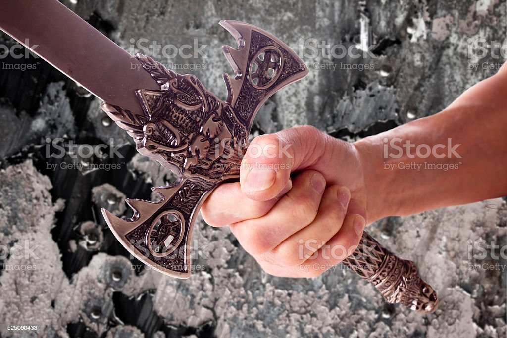 Man holds medieval sword. Rock background. Close-up of hand. stock photo