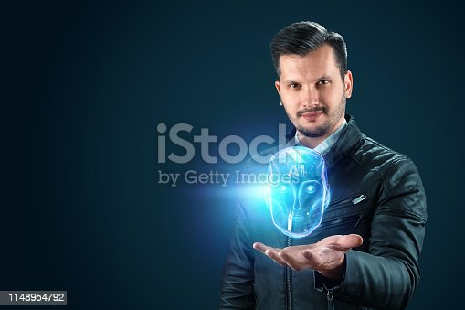 1147918337 istock photo A man holds out a hand with a hologram of a robot head, artificial intelligence on a blue background. Concept neural networks, autopilot, robotization, industrial revolution 4.0. 1148954792