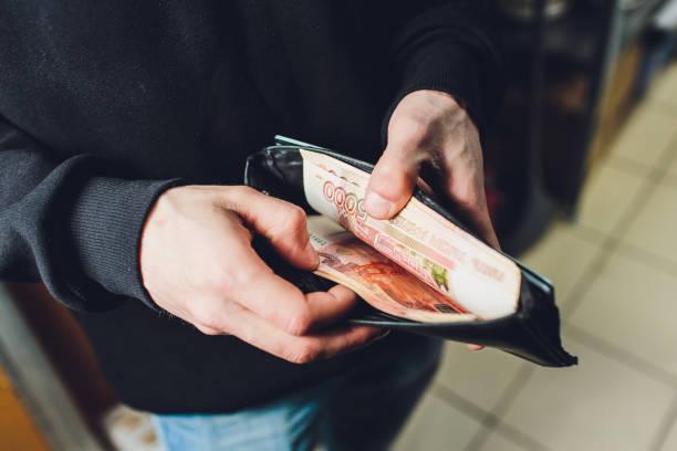 Ein Mann hält Rubel und Dollar in der Hand, ein Geschäftsmann hält Geld in der Hand. – Foto
