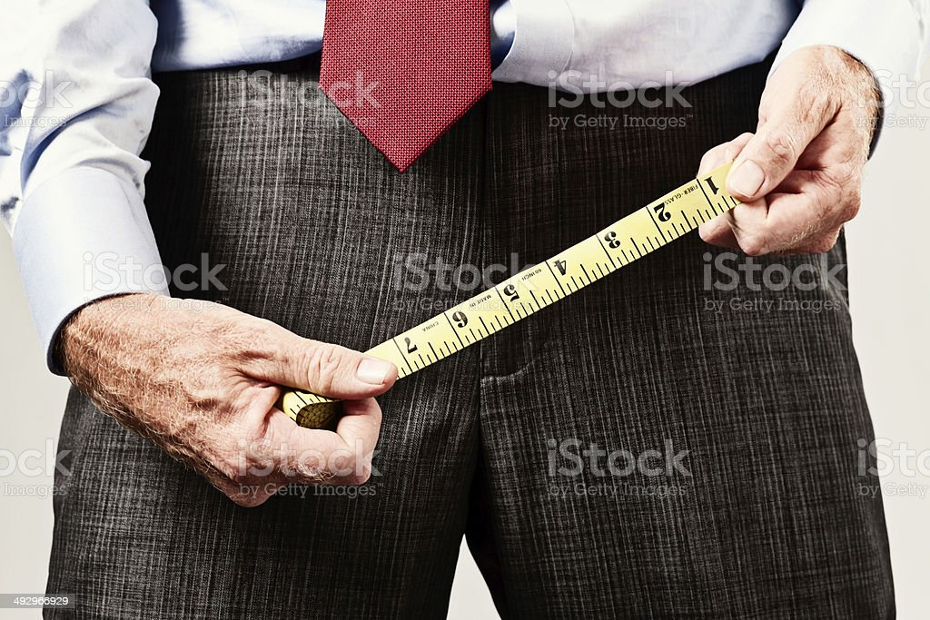 Man holds tape measure over pelvic region, possibly comparing sizes! stock photo